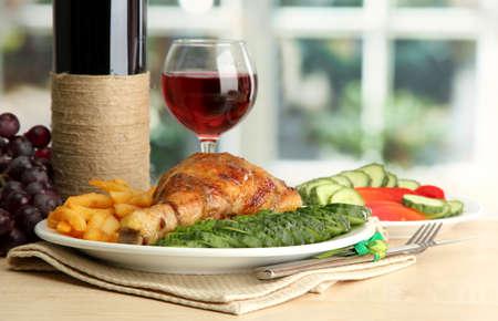 vin chaud: Poulet r�ti avec des frites fran�aises et les concombres, verre de vin sur la table en bois � l'int�rieur caf�