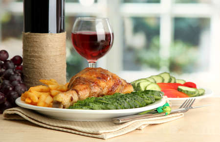 wine food: Roast chicken with french fries and cucumbers, glass of wine on  wooden table in cafe interior