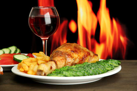 Roast chicken with french fries and cucumbers, glass of wine on wooden table  on fire background Stock Photo - 15116765