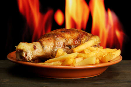Roast chicken with french fries on fire background photo