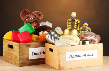 Donation box with food and children's toys on brown background close-up photo