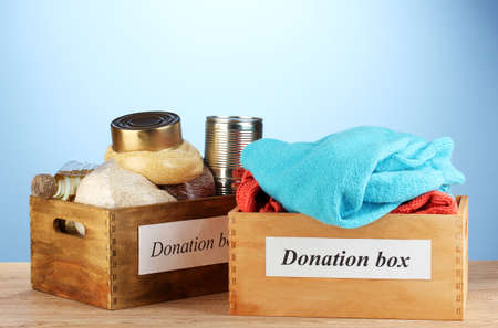 Donation boxes with clothing and food on blue background close-up Stock Photo - 15152792