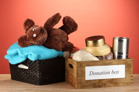 Donation boxes with clothing and food on red background close-up Stock Photo - 15152724