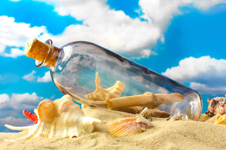 Glass bottle with note inside on sand, on blue sky background Stock Photo