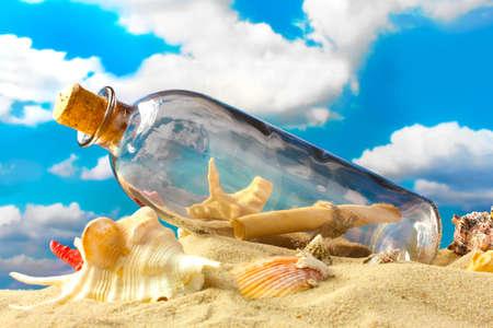 Skleněná láhev s poznámkou uvnitř na písku, na modré obloze na pozadí