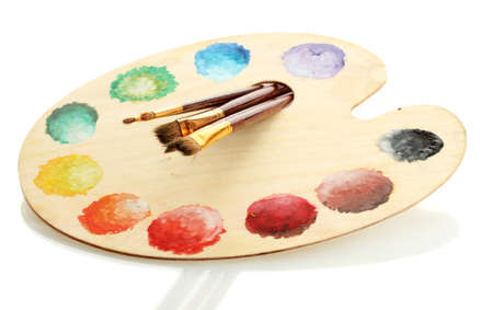 wooden art palette with paint and brushes isolated on white photo