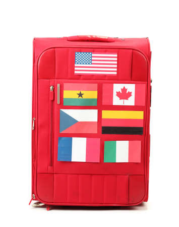 red suitcase with many stickers with flags of different countries isolated on white photo