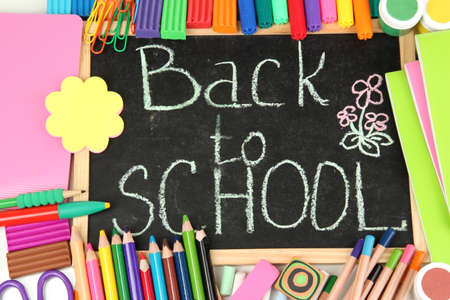 The words 'Back to School' written in chalk on the small school desk with various school supplies close-up Stock Photo - 15153429
