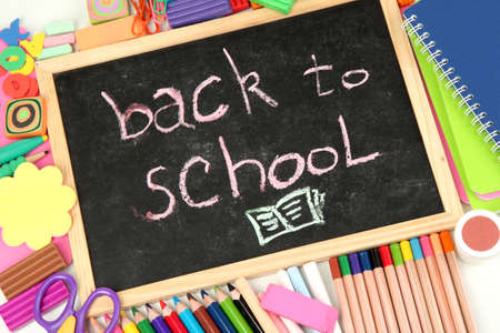 The words 'Back to School' written in chalk on the small school desk with various school supplies close-up photo