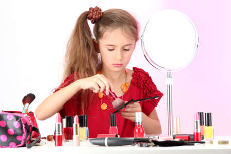 little girl in her mother's dress, is trying painting her face Stock Photo - 15261685