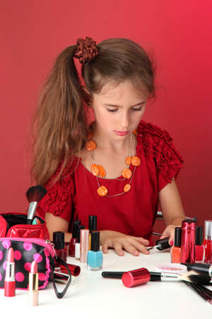 little girl in her mother's dress, is trying painting her nails Stock Photo - 15261691