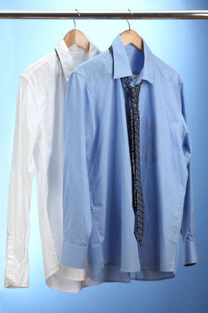 blue and white shirts with tie on wooden hanger on blue background Stock Photo - 15151919