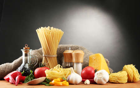 italian pasta: Pasta spaghetti, vegetables and spices, on wooden table, on grey background