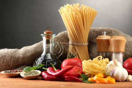 italy food: Pasta spaghetti, vegetables and spices, on wooden table, on grey background