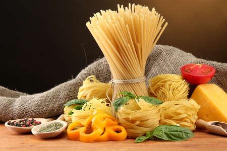 macarrones: Espaguetis pasta, verduras y especias, sobre la mesa de madera, sobre fondo marrón