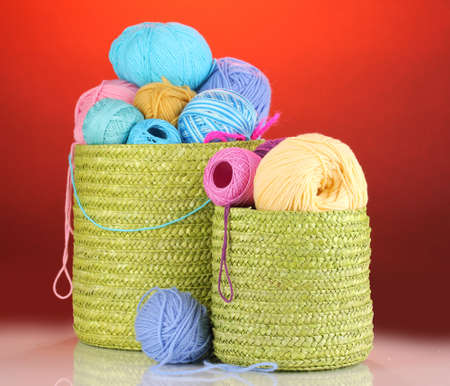 Colorful yarn for knitting in green basket on red background photo