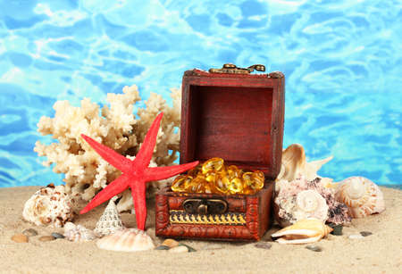 fish oil in the chest on the sand on blue background close-up photo
