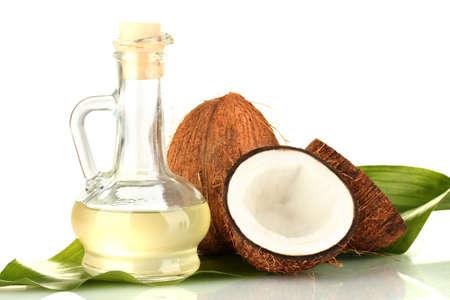 decanter con olio di cocco e noci di cocco isolato su bianco