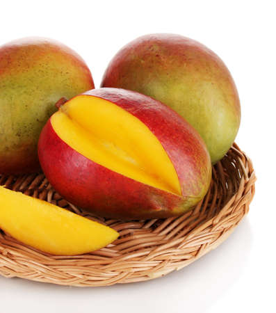 season specific: Ripe appetizing mango on wicker cradle isolated on white Stock Photo