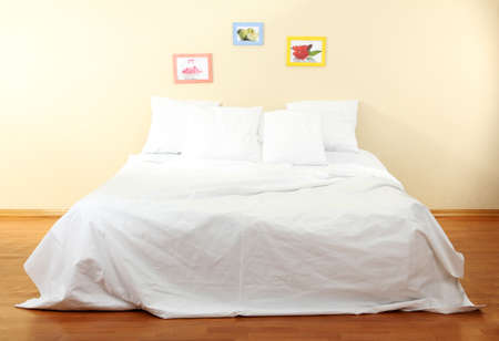 white sheet: Empty bed with pillows and sheets in bedroom
