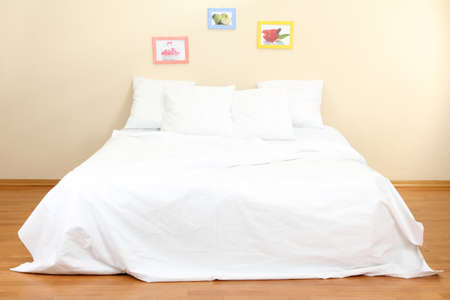 Empty bed with pillows and sheets in bedroom photo