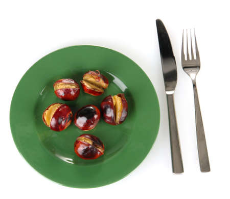 buckeye seed: roasted chestnuts in the green plate with fork and knife isolated on white