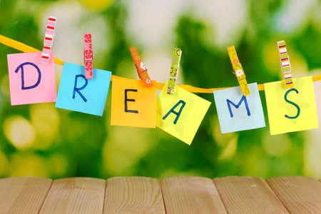 Het woord Dreams op houten tafel op natuurlijke achtergrond
