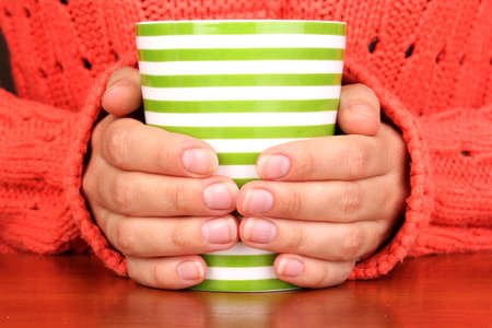 cold weather: hands holding mug of hot drink close-up