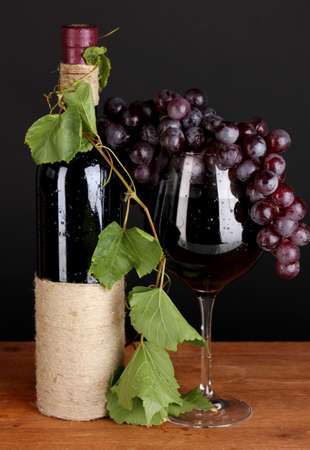 bottle of wine with grape leaves on wooden table on black background photo