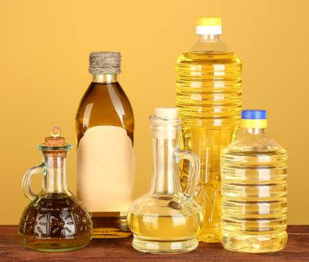 De oliva y aceite de girasol en botellas y jarras pequeñas en fondo amarillo close-up