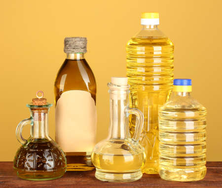 oil seed: Olive and sunflower oil in the bottles and small decanters on yellow background close-up