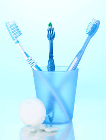 Toothbrush in glass, dental floss and chewing gum on blue background photo