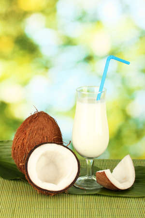 glass of coconut milk and coconuts on green background close-up Stock Photo - 15169463