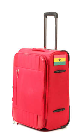 carryall: red suitcase with sticker with flag of Ghana isolated on white
