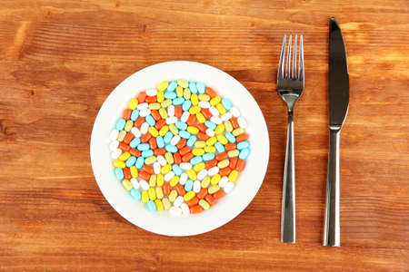 a lot of pills in a plate with knife and fork on wooden background close-up Stock Photo - 15506008