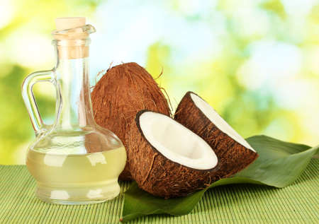decanter with coconut oil and coconuts on green background Фото со стока