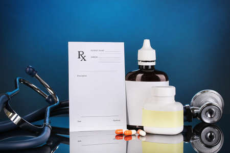 Pharmacist prescription with drops and pills isolated on blue photo