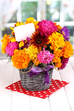 Beautiful bouquet of bright flowers with paper note on wooden table on window background photo