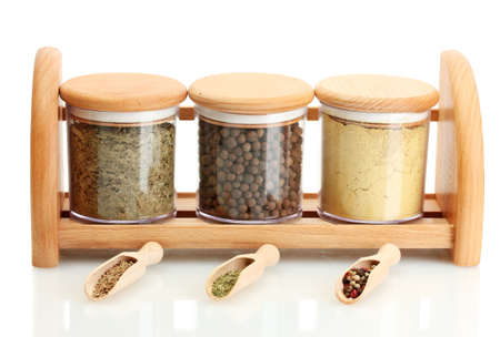 jars and wooden spoons with spices on wooden shelf isolated on white photo