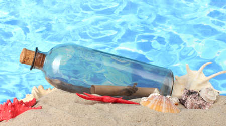 Glass bottle with note inside on sand, on blue sea background photo