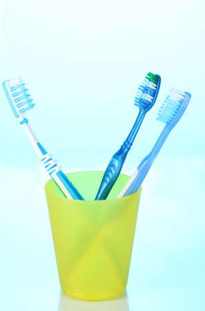 Toothbrushes in glass on blue background photo