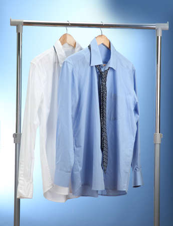 blue and white shirts with tie on wooden hanger on blue background photo