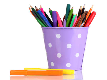 Colorful pencils and felt-tip pens in purple pail isolated on white photo