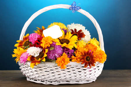 ronantic: Beautiful bouquet of bright flowers in white basket on wooden table on blue background