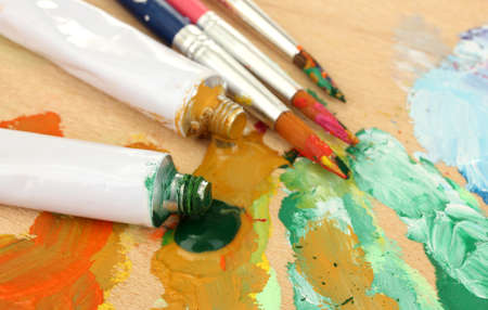 Abstract acrylic paint, paint tubes and brushes on wooden  palette Stock Photo - 15385749