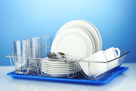 clean kitchen: clean dishes on stand on blue background