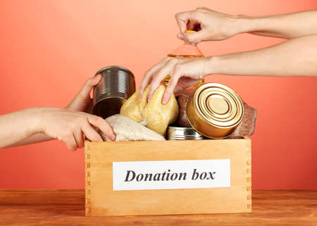 FOOD BOX: Donation box with food on red background close-up
