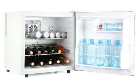 Mini fridge full of bottles of alcoholic beverages and water isolated on white photo