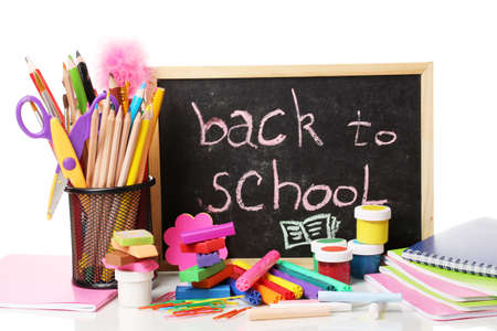 The words 'Back to School' written in chalk on the small school desk with various school supplies close-up isolated on white photo