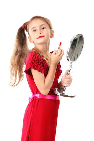 little girl in her mothers dress, is trying painting her lips, isolated on white